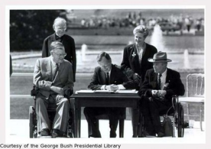 Photo of the ceremonial signing of the Americans with Disabilities Act by President George. H. W. Bush. He is joined by Texan disability advocate Justin Dart.
