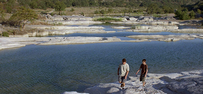 A man and a boy walk along the water of Pedernales Falls