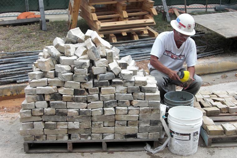 A Worker Cleans Historic Bricks for Reuse