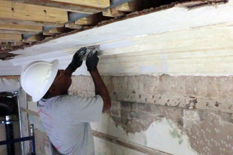 A Worker is Cleaning and Replastering an Interior Mansion Wall
