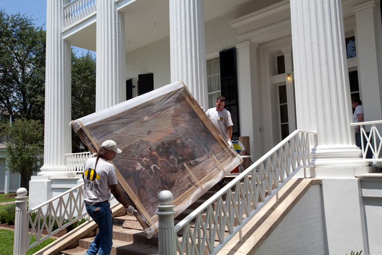 Workers move 18th century painting back to its home in the Mansion