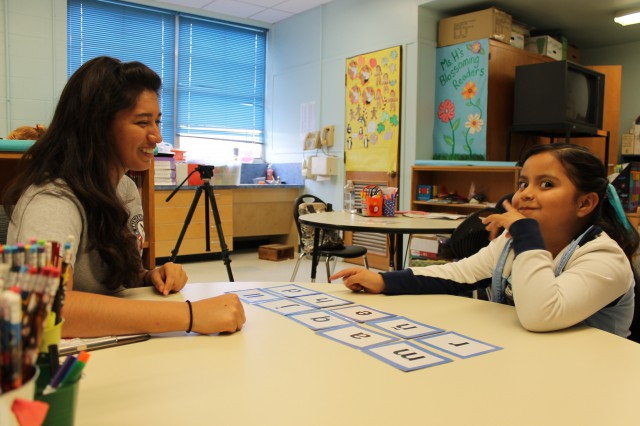 Volunteer works with a child on flashcards in a classroom