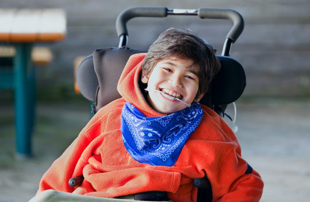Portrait of a child smiling in a wheelchair