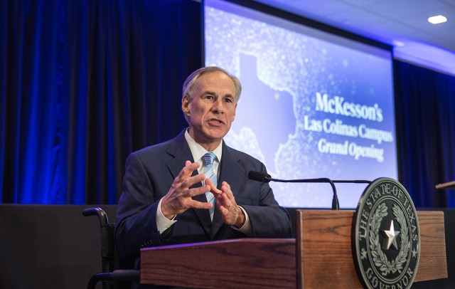 Governor Abbott speaks at a podium with a slide presentation behind him