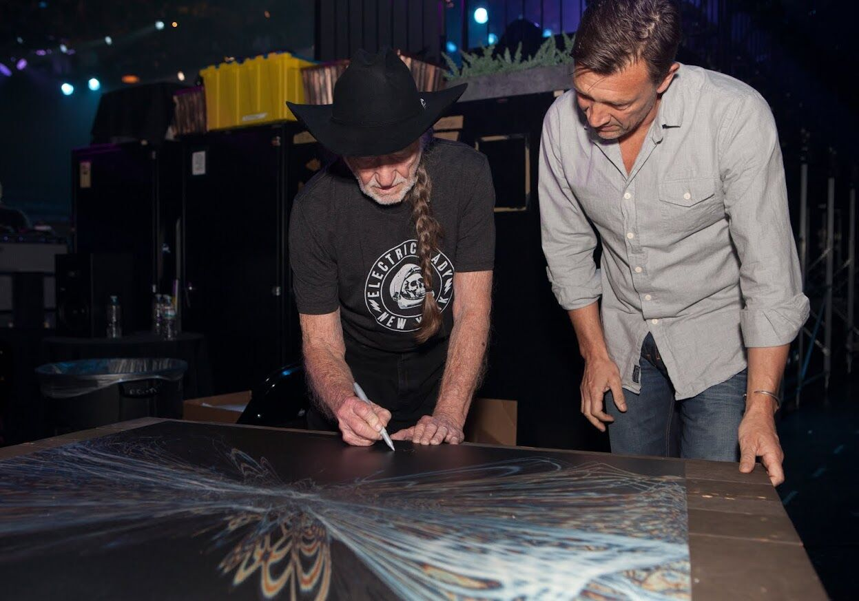 Willie Nelson signs the Soundwaves art with artwork creator Tim Wakefield