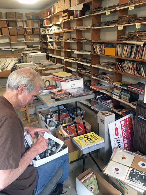 Austin Record Convention founder Doug Hanners sorting through memorabilia at his garage-office headquarters.