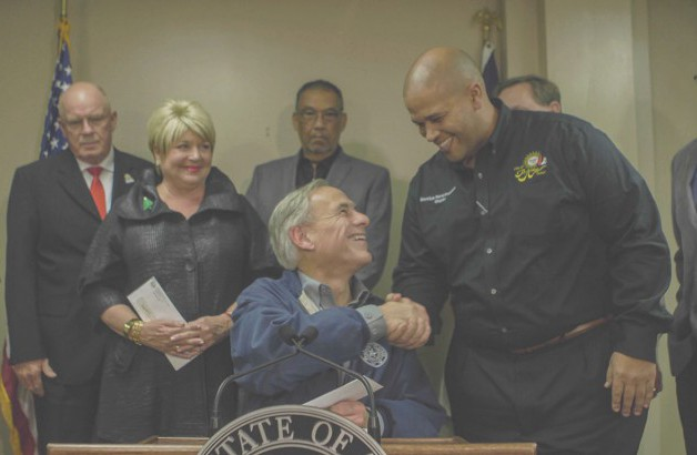 Governor Abbott shakes the hand of local official and presents funds for debris removal.