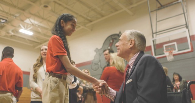 Governor Abbott shakes hands with a student from Briarhill Middle School for the NASA In-Flight Education Downlink.