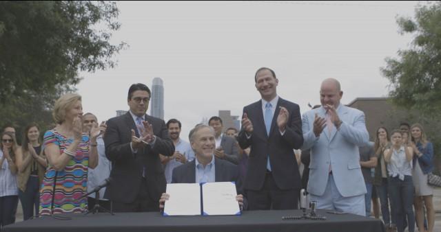 Governor Greg Abbott presents signed bill to end local regulations of transportation network.