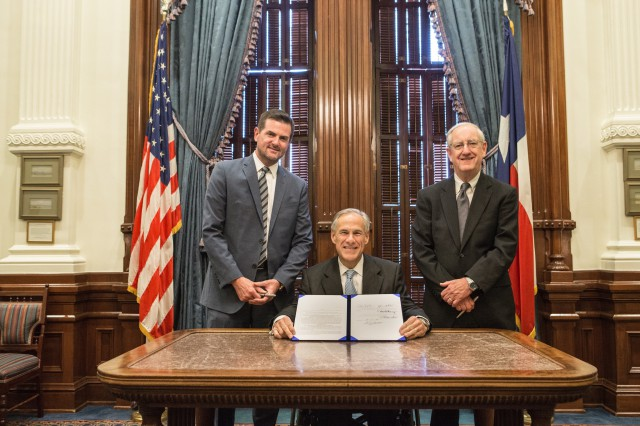 Governor Abbott presents signed House Bill 214.