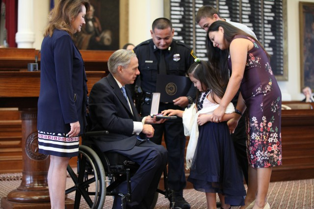 Governor Greg Abbott and First Lady Cecilia Abbott present Star of Texas award to family.