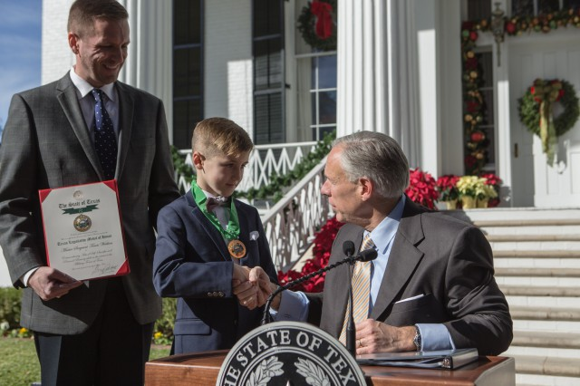 Governor Abbott presents the Texas Legislative Medal of Honor to Master Sergeant Travis Watkins' great grandson.