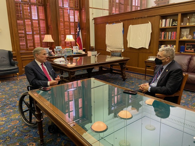 Governor Abbott sitting at a table with DPS Director Steve McCraw.